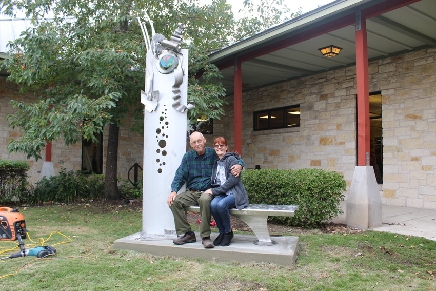 Rollin Karg poses with his fiance Thursday during the installation of his stainless steel art bench at the Leander Public Library.