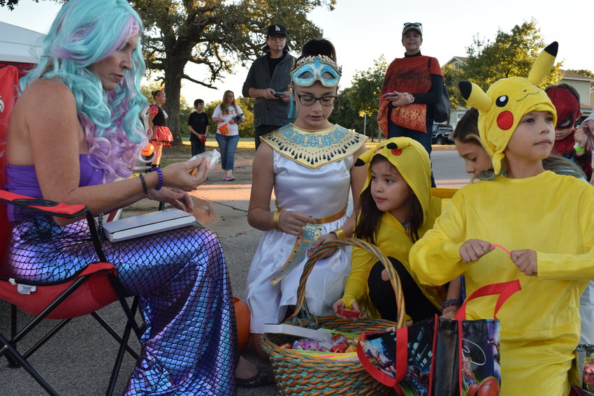 Trick-or-treaters pick out candy given by a mermaid at the Cedar Park Recreation Center's Trunk-or-Treat event on Saturday.