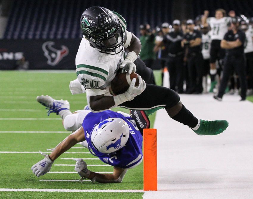Cedar Park Timberwolves sophomore running back Kevin Adams (20) dives across the pylon for a touchdown during the second quarter of a high school football playoff game between Cedar Park and Friendswood at NRG Stadium in Houston, Texas, on Nov. 23, 2019.