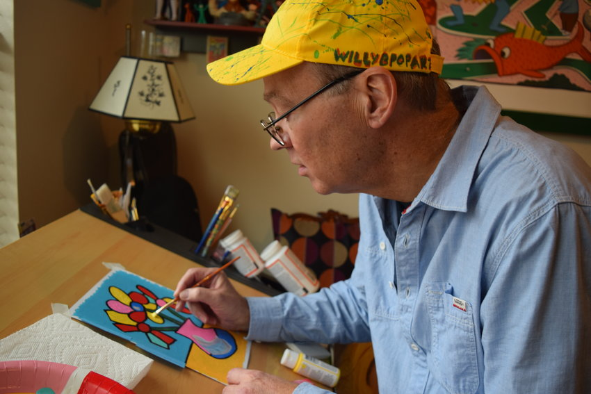 Local pop artist Bill Whiting works on a painting.