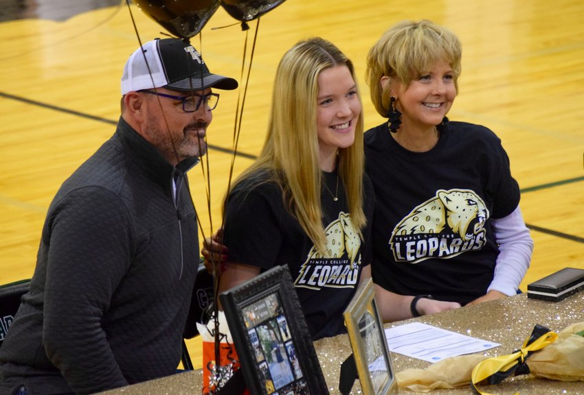 Olivia Meyer, center, signed to play volleyball at Temple College on Wednesday morning. She overcame a pair of knee injuries during her time in Cedar Park.