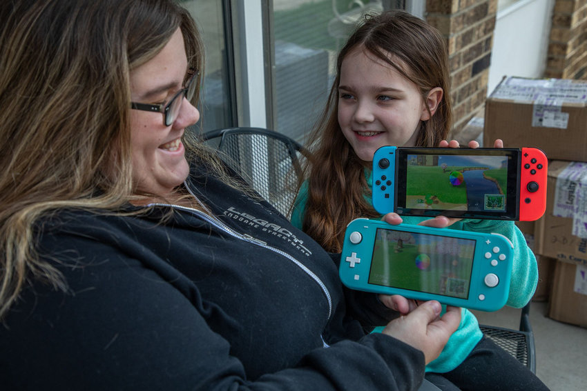 """Amber Gercken and her daughter Lily, 10, play the Nintendo game """"Animal Crossing"""" outside of their home in Mokena on April 6, 2020. They are fans of the hit Nintendo game, which came out just as the coronavirus-related stay-at-home orders were announced. (Zbigniew Bzdak/Chicago Tribune/TNS)"""