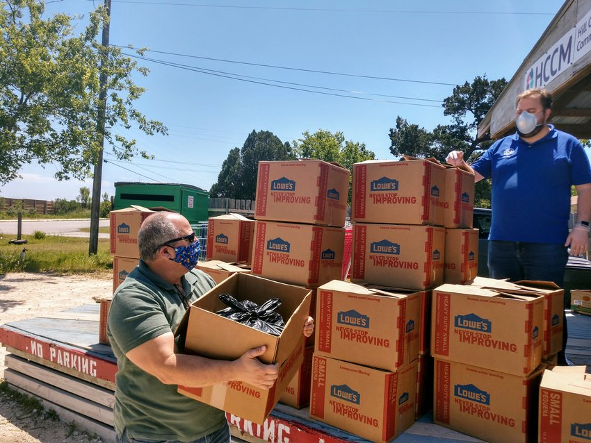Texas House District 136 Rep. John Bucy and Cedar Park City Council member Mel Kirkland worked Thursday loading food boxes into vehicles for deliveries to area seniors outside of Hill Country Community Ministries.