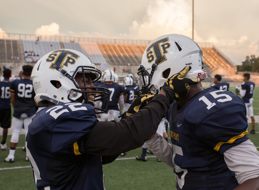 Stony Point Tigers junior defensive back Larry F. King III (22) helps just the helmet of junior defensive back Treshon Pickett (15) during a high school football game between Stony Point High School and Killeen High School at Kelly Reeves Stadium in Round Rock, Texas on August 25, 2016.