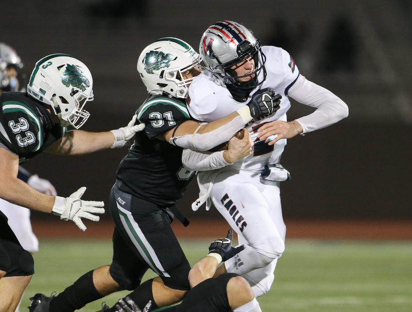 Cedar Park Timberwolves senior linebacker Shelby Battles (31) wraps up Veterans Memorial Eagles quarterback Carter Senterfitt (2) during a high school football playoff game  between Cedar Park and Veterans Memorial on January 8, 2021 in San Antonio, Texas.