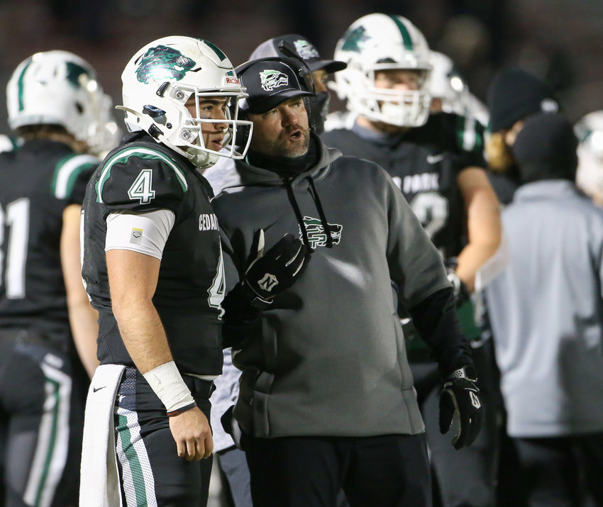Cedar Park Timberwolves head coach Carl Abseck talks with senior quarterback Ryder Hernandez (4) during a high school football playoff game  between Cedar Park and Veterans Memorial on January 8, 2021 in San Antonio, Texas.