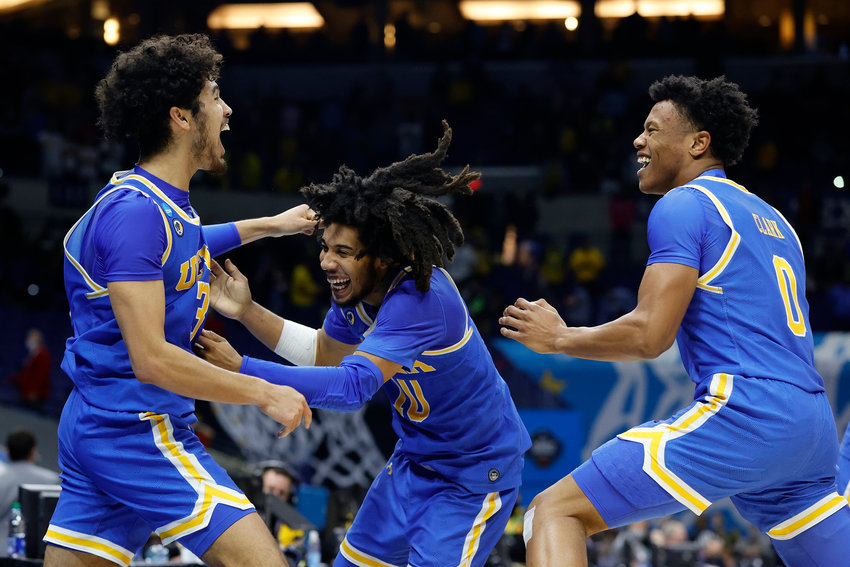 Tyger Campbell #10 of the UCLA Bruins celebrates with Johnny Juzang #3 and Jaylen Clark #0 after defeating the Michigan Wolverines 51-49 in the Elite Eight round game of the 2021 NCAA Men's Basketball Tournament at Lucas Oil Stadium on March 30, 2021, in Indianapolis, Indiana. (Tim Nwachukwu/Getty Images/TNS)