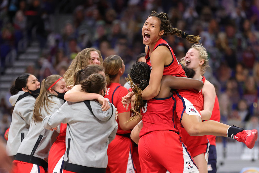 Arizona's Sam Thomas (14) jumps on teammate Trinity Baptiste (0) in celebration of a win against Connecticut in a Final Four semifinal game in the NCAA Tournament at the Alamodome in San Antonio, Texas, on Friday, April 2, 2021. (Carmen Mandato/Getty Images/TNS)