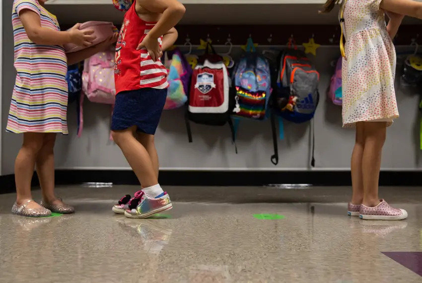 Kindergarten students line up on social distancing markers on the first day of in-person classes at Highland Village Elementary last year.