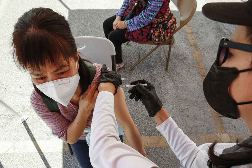 A woman receives a COVID-19 vaccination at a mobile clinic in Los Angeles' Chinatown. (Al Seib/Los Angeles Times/TNS)
