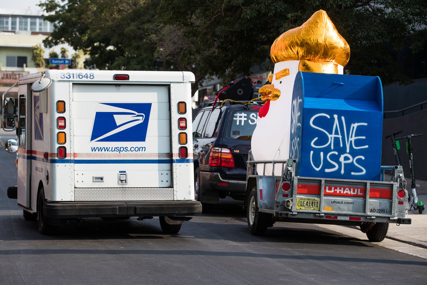 A mail truck is seen as rally-goers gather at a post office to protest the Trump administration's handling of the U.S. Postal System at the Rally to Save the Post Office on August 22, 2020 in Los Angeles, California. (Rich Fury/Getty Images for MoveOn/TNS)