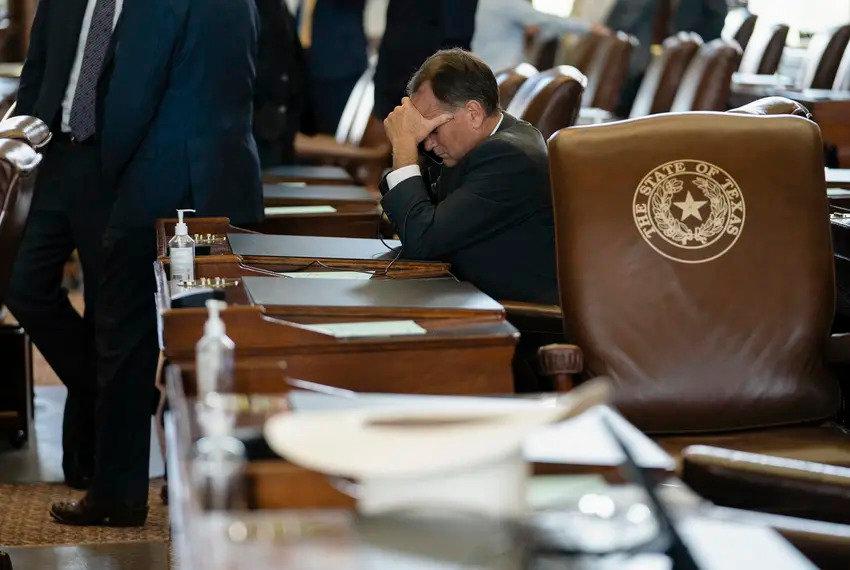 A legislator talks on the phone from a desk on the Texas House floor on July 19.
