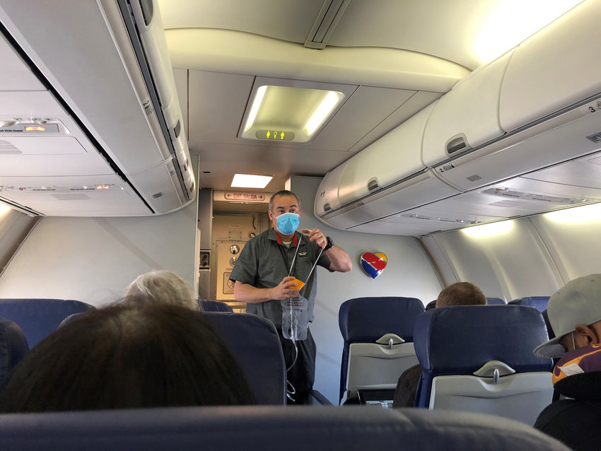 A flight attendant, wearing one mask, demonstrates the use of an oxygen mask at the outset of flight from Burbank to Las Vegas in June. A survey of flight attendants found unruly passengers are an ongoing problem. (Christopher Reynolds/Los Angeles Times/TNS)