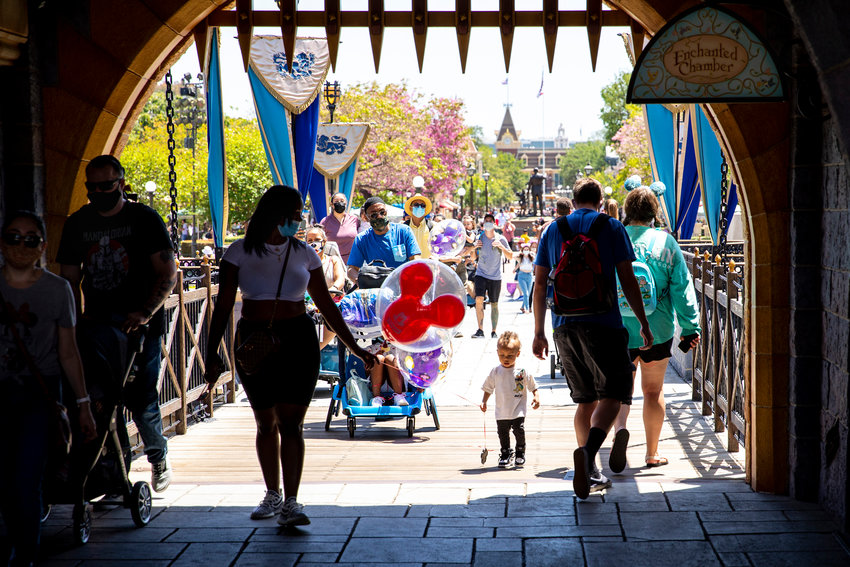 Visitors pass through Sleeping Beauty Castle at Disneyland Resort in Anaheim, Calif., as visitors return to the park with COVID-safety restrictions in place on May 3, 2021. (Jay L. Clendenin/Los Angeles Times/TNS)