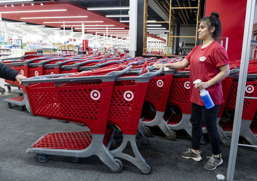 An employee sanitizes shopping carts at the entrance on March 29, 2020 at Target in Chicago's Logan Square neighborhood. (Brian Cassella/Chicago Tribune/TNS)