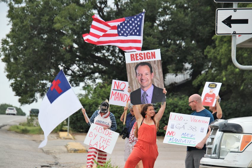 Protested lined the side of U.S. Highway 183 at its intersection with RM 2243 in Leander on Wednesday, Aug. 18, 2021, to voice their opposition to Leander ISD's recent face mask mandate.