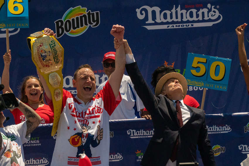 """Competitive eating champion Joey """"Jaws"""" Chestnut wins the 2021 Nathan's Famous 4th of July International Hot Dog Eating Contest with 76 hot dogs, breaking his personal best record of 75 at Coney Island on July 4, 2021 in New York City.  (David Dee Delgado/Getty Images/TNS)"""