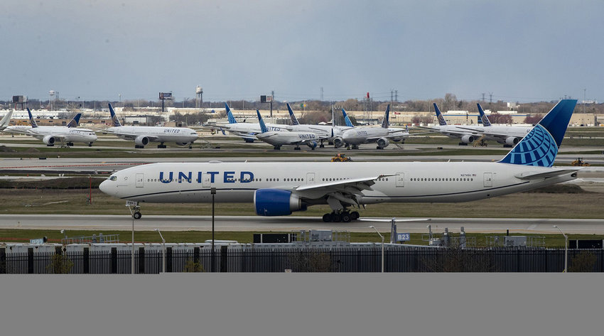 A United Airlines plane taxis by parked United jets at O'Hare International Airport in Chicago on April 14, 2020. (Brian Cassella/Chicago Tribune/TNS)