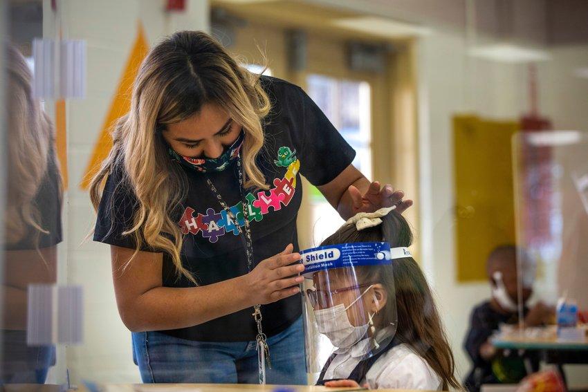 Student teacher Karen Martinez-Calderon, left, fastens a face shield onto Anastacia Valdez after lunch at N.W. Harllee Early Childhood Center in the Oak Cliff neighborhood of Dallas on Friday, October 2, 2020. (Lynda M. González/The Dallas Morning News/TNS)