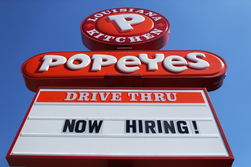 A 'Now Hiring' sign is posted in front of a Popeye's restaurant on February 04, 2021, in Miami, Florida. The Labor Department announced weekly unemployment claims unexpectedly rose last week, led by a surge in claims in California. (Joe Raedle/Getty Images/TNS)
