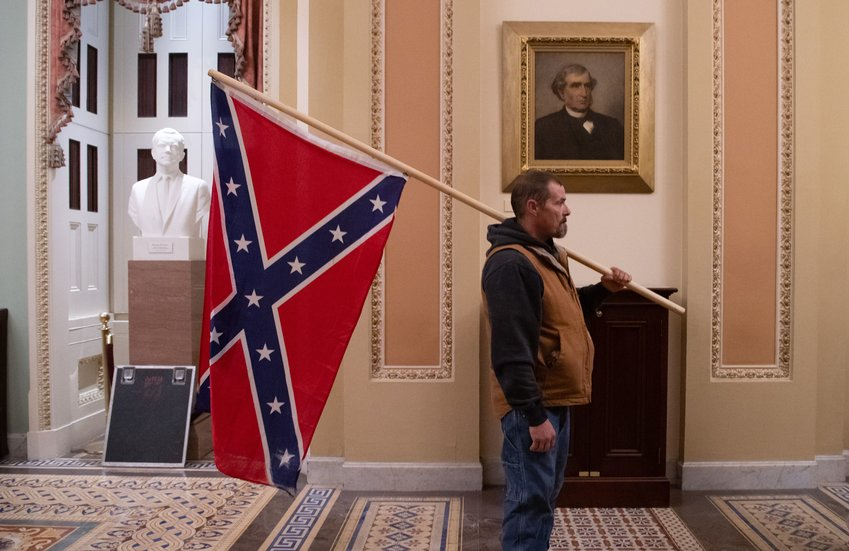 A supporter of President Donald Trump holds a Confederate flag outside the Senate Chamber during a rampage in the U.S. Capitol in Washington, D.C., on Jan. 6, 2021. (Saul Loeb/AFP via Getty Images/TNS)