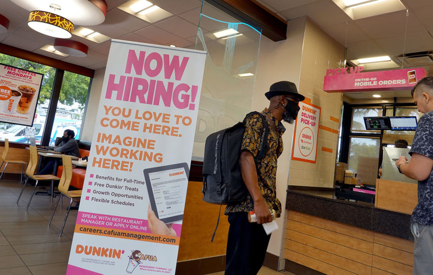 """A """"Now Hiring"""" sign is displayed at a Dunkin' restaurant on Sept. 21, 2021 in Hallandale, Florida. (Joe Raedle/Getty Images/TNS)"""