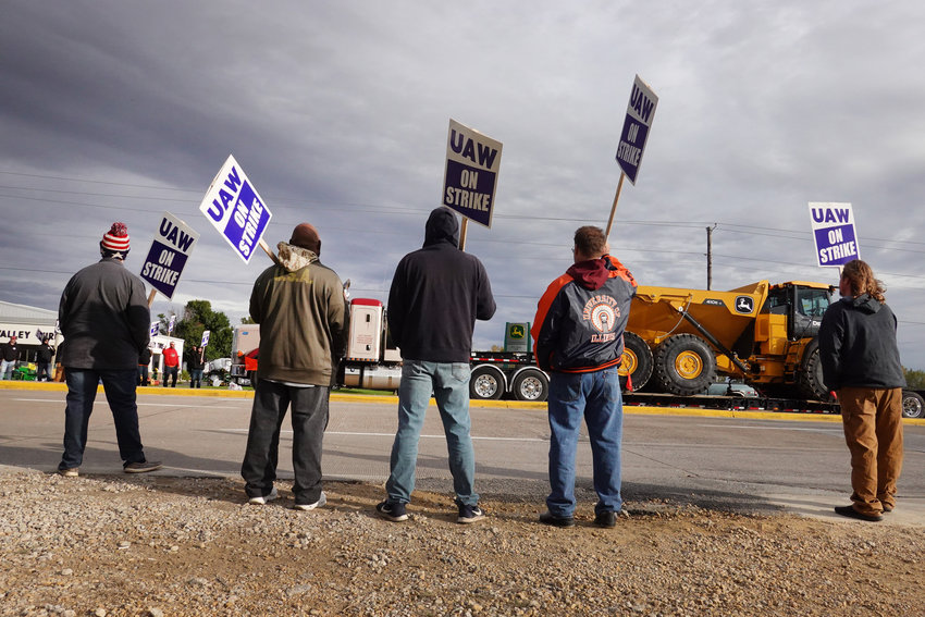 A truck hauls a piece of John Deere equipment from the factory past workers picketing outside of the John Deere Davenport Works facility on Oct. 15, 2021 in Davenport, Iowa. More than 10,000 John Deere employees, represented by the UAW, walked of the job at yesterday after failing to agree to term of a new contract. (Scott Olson/Getty Images/TNS)