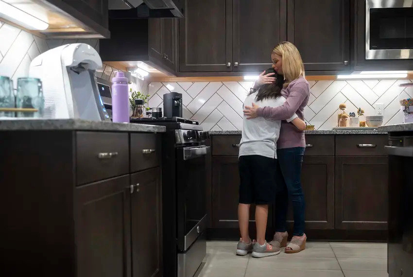 Danielle Miller hugs her child as the family prepares for school at their home in Magnolia. The ACLU of Texas is suing the Magnolia school district on behalf of Miller's child and other students over its long-hair policy. Credit: Annie Mulligan for The Texas Tribune