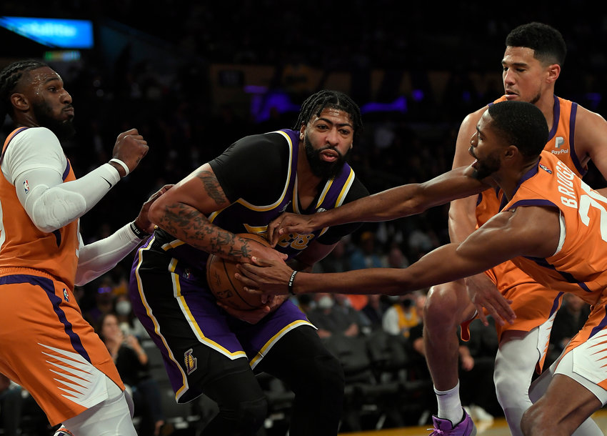 The Los Angeles Lakers' Anthony Davis (3) is surrounded by the Phoenix Suns' Mikal Bridges (25), Jae Crowder (99) and Devin Booker (1) during the first half at Staples Center on Friday, Oct. 22, 2021, in Los Angeles. The Suns topped the Lakers, 115-105 in a game that was marred by a scrum between Davis and Dwight Howard on the Lakers' bench. (Kevork Djansezian/Getty Images/TNS)
