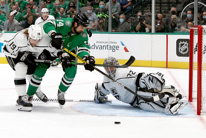 The Dallas Stars' Jamie Benn (14) puts a shot on Los Angeles Kings goaltender Jonathan Quick (32) under pressure from the Kings' Alex Iafallo (19) in the first period at American Airlines Center on Friday, Oct. 22, 2021, in Dallas. (Tom Pennington/Getty Images/TNS)