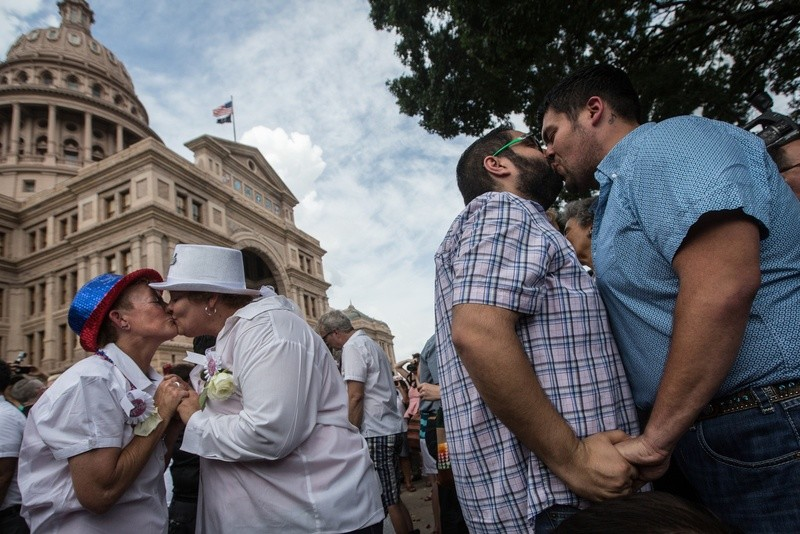 "Couples embrace at the conclusion of the ""Big Gay Wedding"" ceremony on the south lawn of the Texas Capitol on July 4 after the Supreme Court legalized same-sex marriage in June."