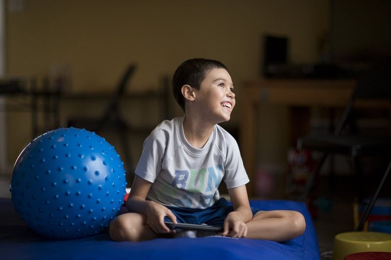 Octavio Armendariz, 8, smiles as he watches cartoons on his iPad in his living room at his home in El Paso, Texas. Octavio has moderate-to-severe autism and severe attention deficit hyperactivity disorder (ADHD).