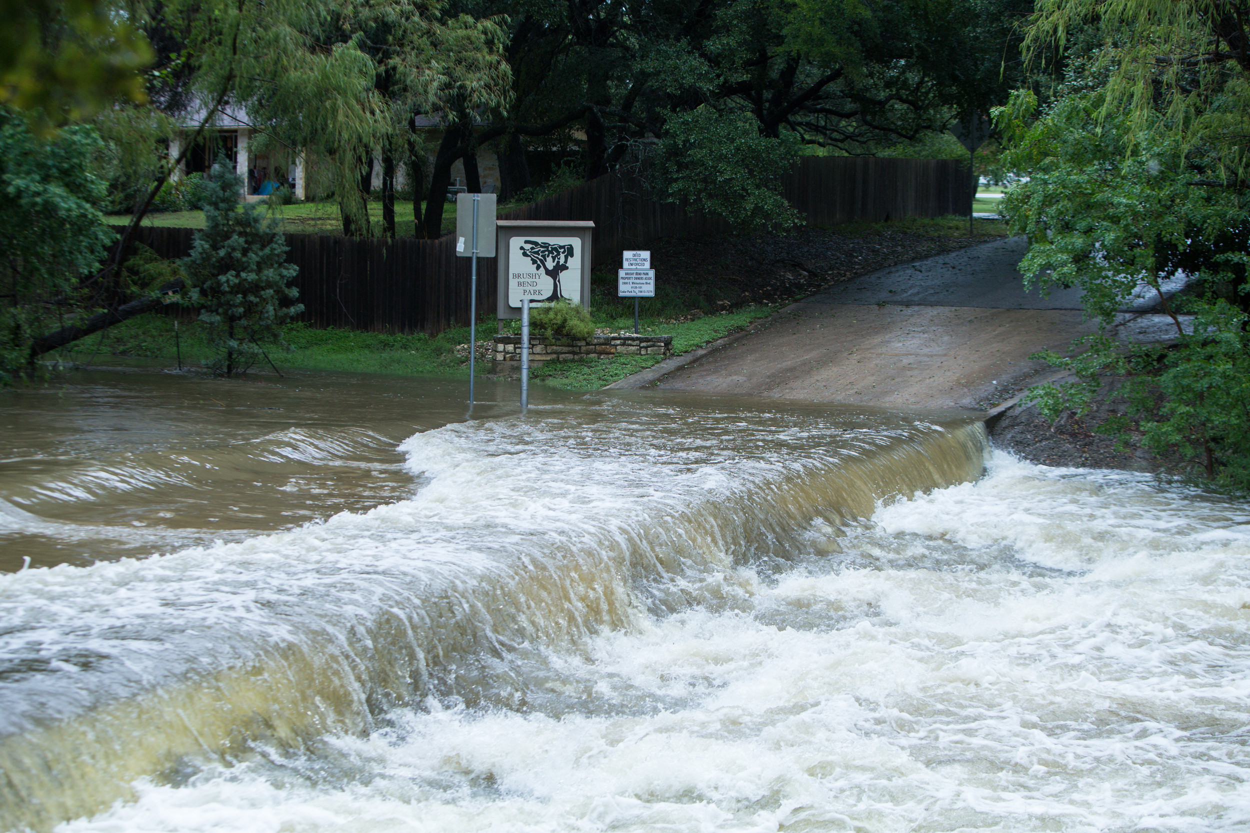Water from Brushy Creek floods over Brushy Bend Drive in Round Rock on Sunday afternoon, Aug. 27.