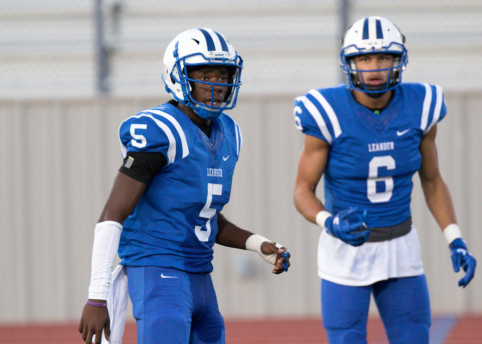 Leander Lions senior quarterback Rashad Carter (5) and senior wide receiver Dalton Flowers (6) look to the sidelines for the offensive play call during a high school football game between Leander and Pflugerville at Bible Stadium in Leander, Texas on Thursday, September 7, 2017.