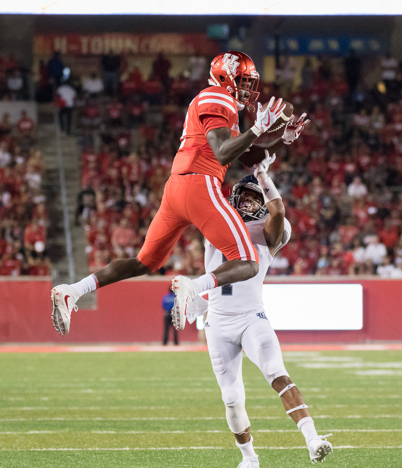 Houston Cougars wide receiver Courtney Lark (9) leaps to make a catch over the defense of Rice Owls cornerback Justin Bickham (7) during the third quarter of the college football game between the Houston Cougars and the Rice Owls at TDECU Stadium in Houston, Texas.