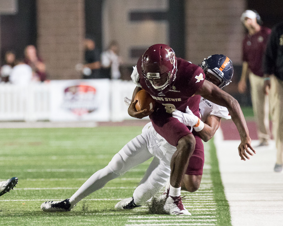 Texas State Bobcats quarterback Willie Jones III (8) is pushed out of bounds by UTSA Roadrunners safety Grant Merka (26) during an NCAA football game between the Texas State Bobcats and the UTSA Roadrunners at Bobcat Stadium in San Marcos, Texas.