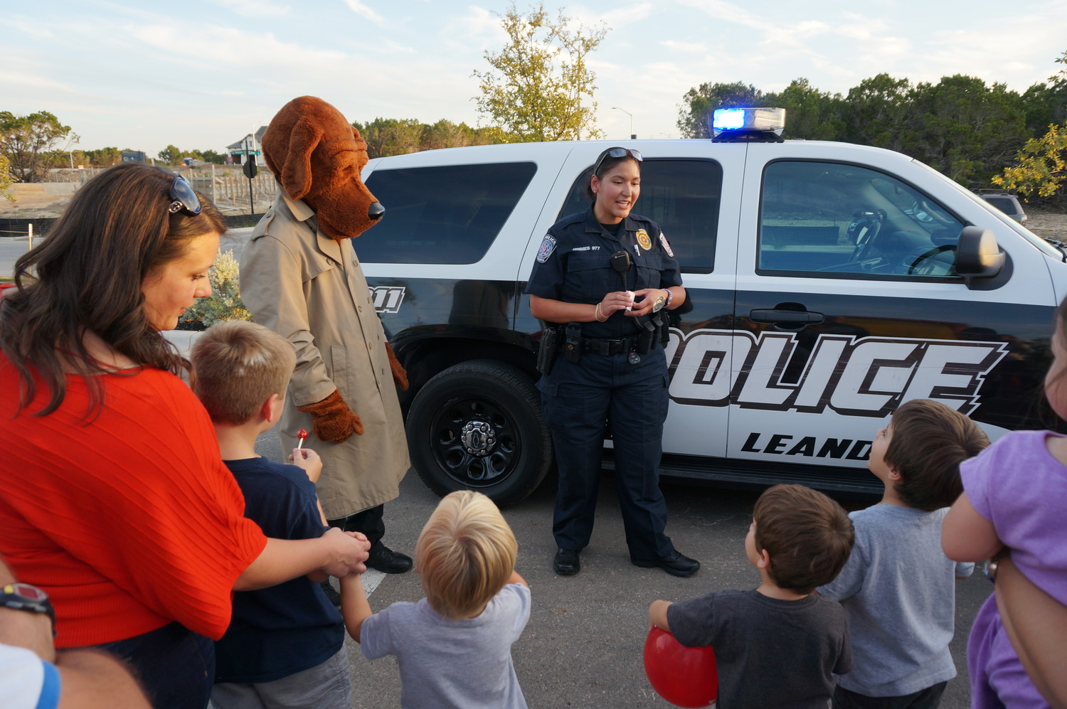 McGruff the crime dog mascot looks on as Leander police officers answer questions from the crowd at National Night Out kick off, Oct. 7, 2015.