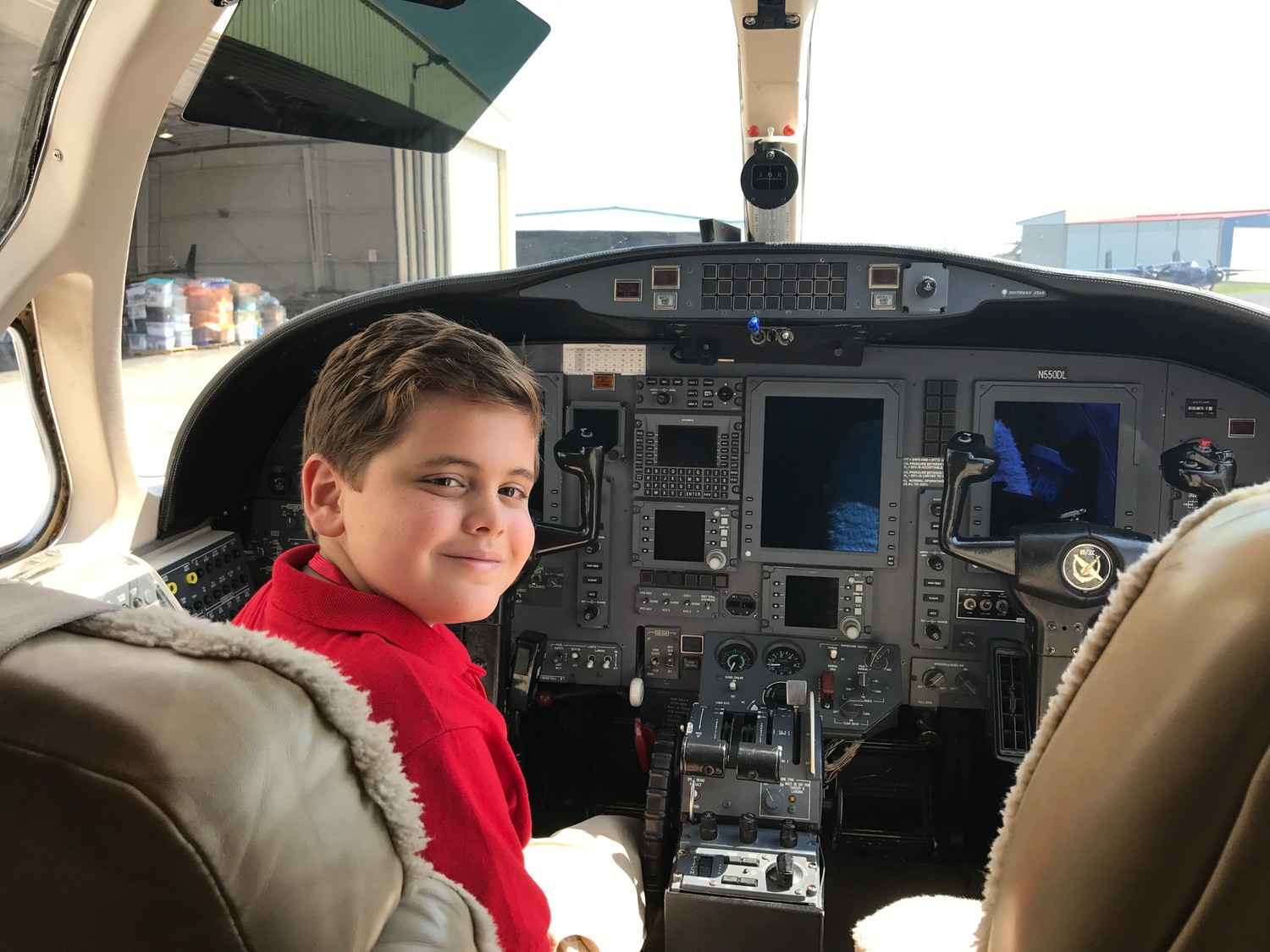 Scholastic News Kid Reporter Truman J. Hamade sits in the cockpit of an airplane loaded with supplies for people affected by Hurricane Harvey in Houston. Truman visited the Georgetown Municipal Airport to learn more about the Austin Disaster Relief Network, a group of volunteers that is collecting food, water, and toiletries for survivors.