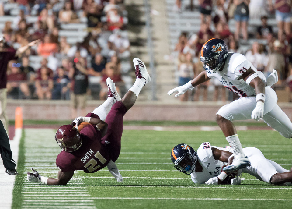 Texas State Bobcats running back Anthony Smith (21) goes down after being tripped by ]UTSA Roadrunners cornerback Javontavius Mosley (28) during an NCAA football game between the Texas State Bobcats and the UTSA Roadrunners at Bobcat Stadium in San Marcos, Texas.