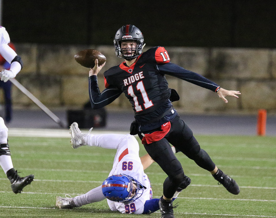 Vista Ridge Rangers senior quarterback Jacob Taute (11) gets a pass off while being brought down by Hays Rebels senior Ryan Leal (99) during a high school football game between the Vista Ridge Rangers and the Hays Rebels at Gupton Stadium in Cedar Park, Texas, on October 27, 2017.
