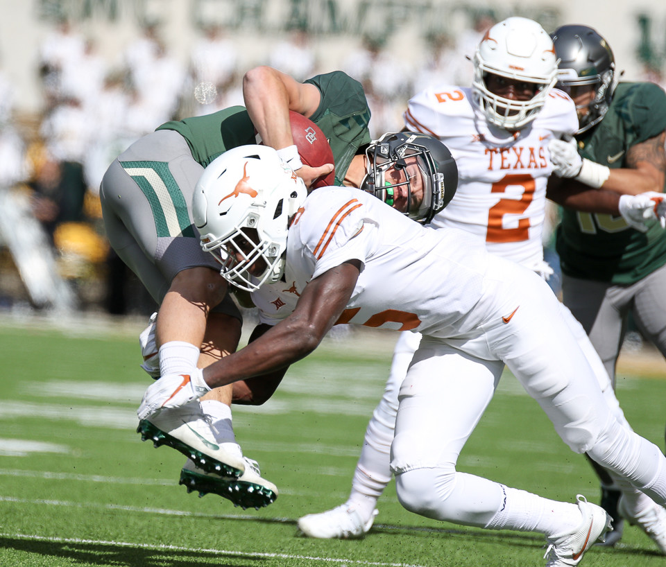 Baylor Bears quarterback Charlie Brewer (12) is tackled by Texas Longhorns defensive back Holton Hill (5) during the first quarter of a college football game between the Baylor Bears and the Texas Longhorns at McLane Stadium in Waco, Texas.