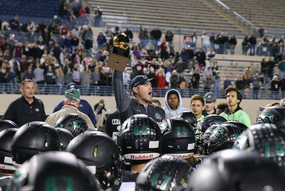 Cedar Park Timberwolves head coach Carl Abseck holds the area round trophy following Cedar Park's 17-14 win over Ennis in the second round of the Class 5A Division I playoffs at Waco ISD Stadium in Waco, Texas, on November 24, 2017.