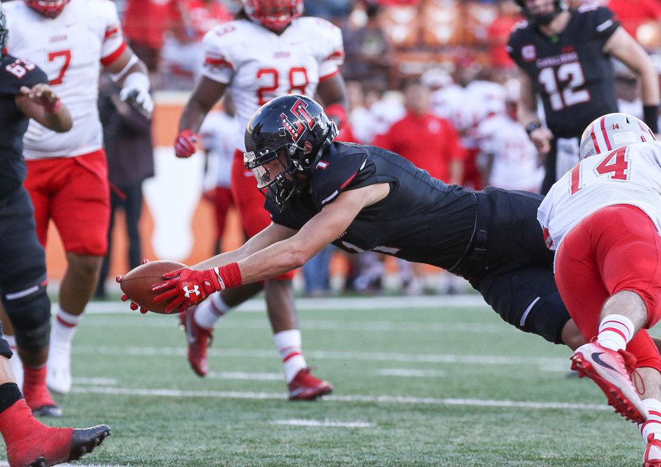 Lake Travis Cavaliers wide receiver Hudson Card (1)  extends the ball as he dives into the end zone for a touchdown during a high school football playoff game between the Lake Travis Cavaliers and the Judson Rockets at DKR Texas Memorial Stadium in Austin, Texas, on November 25, 2017.