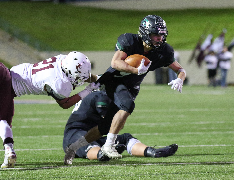 Cedar Park Timberwolves junior Will Lipscomb (9) carries the ball as Ennis Lions senior linebacker Brayan Gonzalez (21) holds on to his jersey during a high school football playoff game between the Cedar Park Timberwolves and the Ennis Lions at Waco ISD Stadium in Waco, Texas, on November 24, 2017.