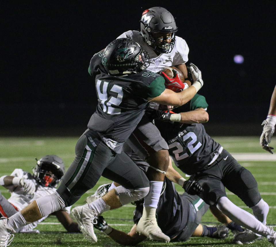 Cedar Park Timberwolves senior Jackson Buckingham (42) and senior Bradly Lovell (22) work to bring down Manvel Mavericks running back Garrison Johnson (2) during a high school football playoff game between the Cedar Park Timberwolves and the Manvel Mavericks at Waller ISD Stadium in Waller, Texas, on December 1, 2017. Manvel won 56-17.
