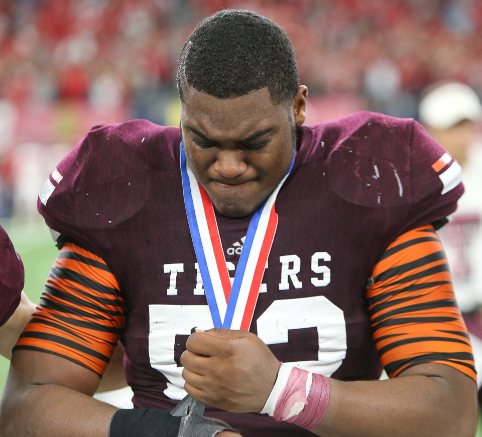 Tenaha Tigers junior Jaurmez Brock (52) unwraps his wrist tape after receiving his silver medal following a 27-20 loss to Muenster High School in the UIL Class 2A Division II state football championship game at AT&T Stadium in Arlington, Texas, on December 21, 2017.