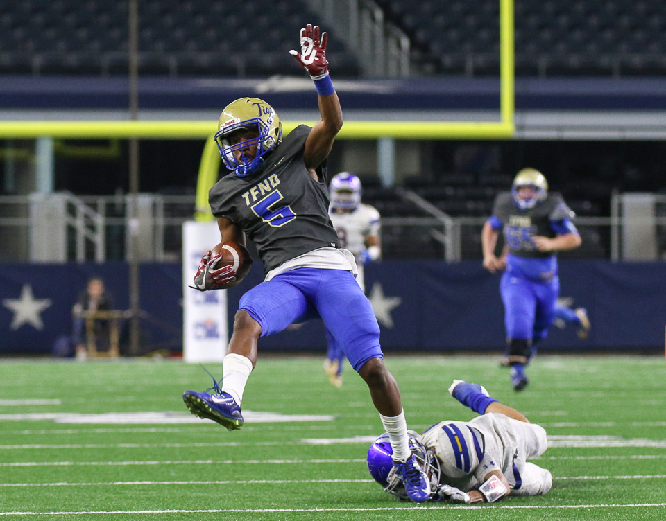 Rockdale Tigers senior Jaquayln Crawford (5) escapes the grasp of Brock Eagles senior Tanner Patino (28) after a reception and scores on the play in the second quarter of the UIL Class 3A Division I state football championship game between Rockdale High School and Brock High School at AT&T Stadium in Arlington, Texas, on December 21, 2017.