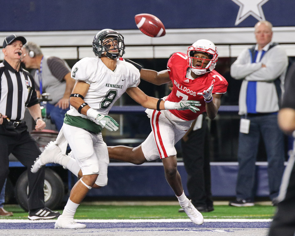 Carthage Bulldogs senior wide receiver Dewaylon Ingram (7) looks in a touchdown pass over Kennedale Wildcats sophomore Spencer Roof (8) during the UIL Class 4A Division I state football championship game between Carthage High School and Kennedale High School at AT&T Stadium in Arlington, Texas, on December 22, 2017.