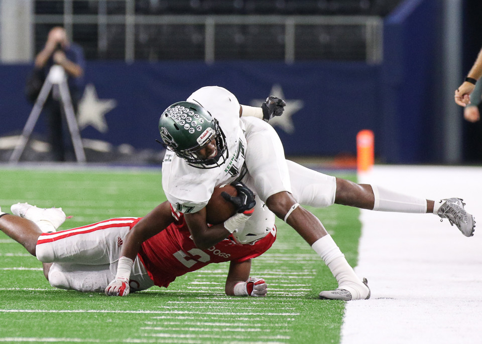 Carthage Bulldogs junior defensive back Jacorey Ware (2) forces Kennedale Wildcats junior Jaden Smith (17) out of bounds during the UIL Class 4A Division I state football championship game between Carthage High School and Kennedale High School at AT&T Stadium in Arlington, Texas, on December 22, 2017.