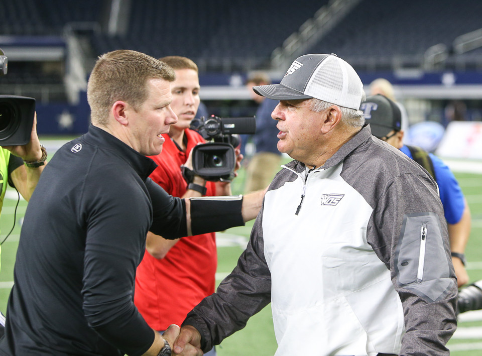 Pleasant Grove Hawks head coach Josh Gibson (left) meets West Orange-Stark Mustangs head coach Cornel Thompson at midfield following the UIL Class 4A Division II state football championship game between West Orange-Stark High School and Pleasant Grove High School at AT&T Stadium in Arlington, Texas, on December 22, 2017.
